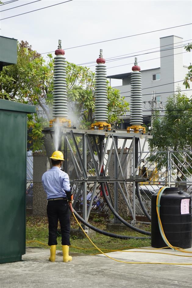台電人員示範絕緣礙子清洗作業,定期清洗礙子可確保供電穩定
